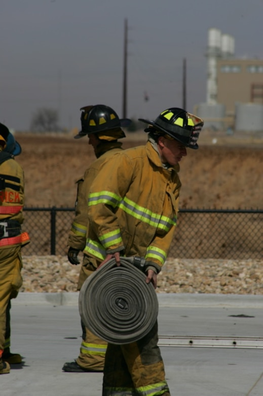 Senior Airman Darrell Linkus, explosive ordnance disposal operator with the 140th Explosive Ordnance Disposal Flight, 140th Wing, Colorado Air National Guard, carries a fire hose while training for his full-time job as a firefighter with the Westminster Fire Department. (Photo courtesy of Senior Airman Darrell Linkus)