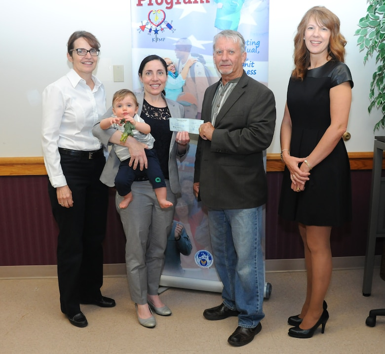 Dennis Brochey (center), Lewiston Town Supervisor presents a check on behalf of the Red Brick Bench Press Championships  to Gina Pizziconi Cupples , president, Friends of Family Support Association, Patty Braun (far left), executive officer, 914th Airlift Wing, and Holly Curcione (far right), executive administrative assistant, Niagara Military Affairs Council, at the Niagara Falls Air Reserve Station on June 5, 2015. More than $11,000 was raised to assist the FFSA, Armed Forces members and their families. (U.S. Air Force photo by Staff Sgt. Matthew Burke)