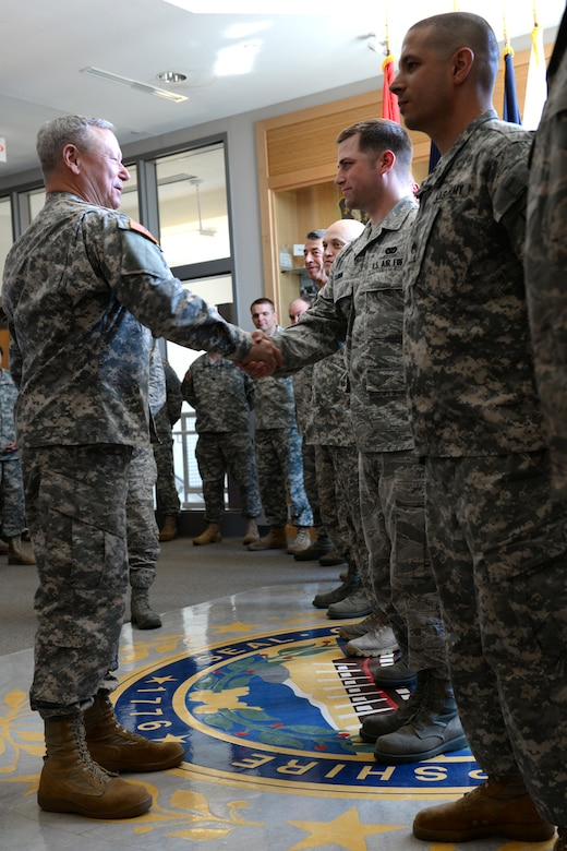 Gen Frank Grass, chief of the National Guard Bureau, presents a commander's coin to Tech. Sgt. Mark Quinn, 157th Civil Engineering Squadron, during a May 3 visit to Joint Force Headquarters in Concord, N.H. (Photo by Senior Airman Kayla McWalter, 157 ARW Public Affairs)