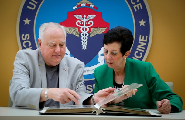 Ray Snedegar and Regina Aune look through a scrapbook of photos and articles collected by Snedegar on Operation Babylift prior to Aune's presentation at the U.S. Air Force School of Aerospace Medicine June 4. (Photo courtesy of Cox Media Group Ohio)