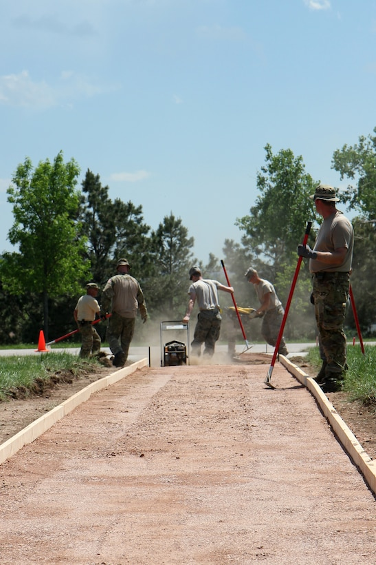 Airmen with the South Dakota Air National Guard's 114th Civil Engineer Squadron of Sioux Falls, S.D., work with members of the Danish Army to construct a sidewalk across the parade field on Camp Rapid in Rapid City, S.D., June 9, 2015. The project is part of the squadron's training for the Golden Coyote exercise.(Army National Guard photo by PFC Kristin Lichius/Released)