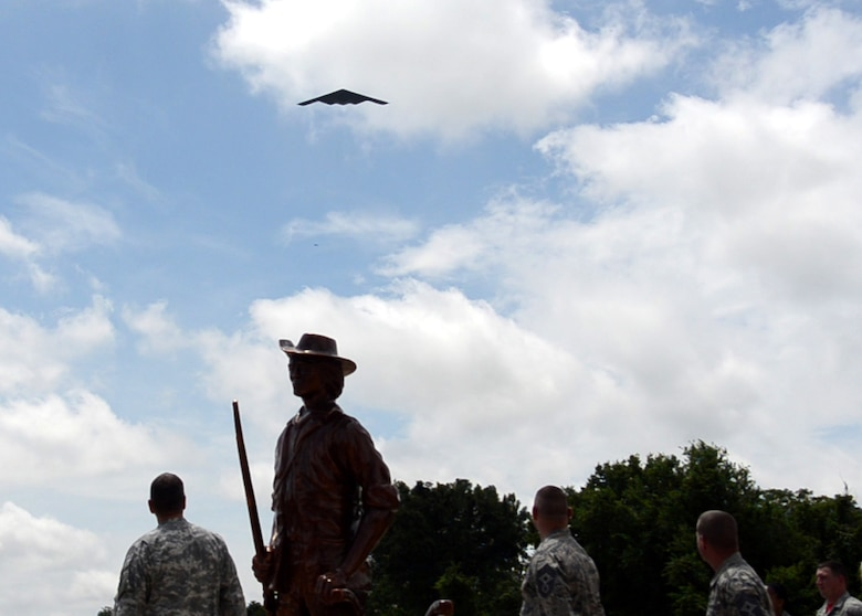 The B-2 Spirit stealth bomber flies overhead the newly-dedicated 131st Bomb Wing Heritage Park as Maj. Gen. Steve Danner, adjutant general of Missouri, Chief Master Sgt. Paul Joseph Sluder, Missouri Air National Guard command chief, and Chief Master Sgt. Paul Carney, 131st Bomb Wing command chief, look on at Whiteman Air Force Base, Mo., June 12, 2015.  The ceremony dedicated three jets that have been a part of the 131st culture and are now a permanent part of Whiteman.