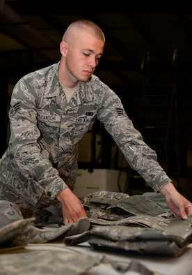 U.S. Air Force Senior Airman Vadim Poleanschi, a 386th Expeditionary Logistic Readiness Squadron logistic specialist, disassembles an individual protective armor at an undisclosed location in Southwest Asia on June 3, 2015. Poleanschi joined the AF for the opportunity of career and personal progression. (U.S. Air Force photo by Senior Airman Racheal E. Watson/Released)
