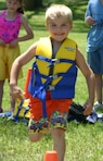 A child having fun running the life jacket relay race during a water safety event.