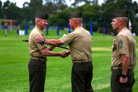 Sergeant Major William T. Sowers receives a Marine non-commissioned officer's sword as he takes over the role of 1st Marine Division Sergeant Major during a relief and appointment ceremony aboard Marine Corps Base Camp Pendleton, Calif., June 12, 2015. Sowers most recently served as the sergeant major for the Marine Corps Training and Education Command in Quantico, Va.