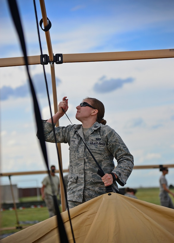 U.S. Air Force Capt. Jessica Pitts, 27th Special Operations Comptroller Squadron budget chief, hoists a canvas tent to attach to its frame during an exercise June 8, 2015 at Melrose Air Force Range, New Mexico. During the exercise, finance and contracting Air Commandos received financial training and practiced managing contracts and contract personnel in a contingency environment. (U.S. Air Force photo/Senior Airman Chip Slack)