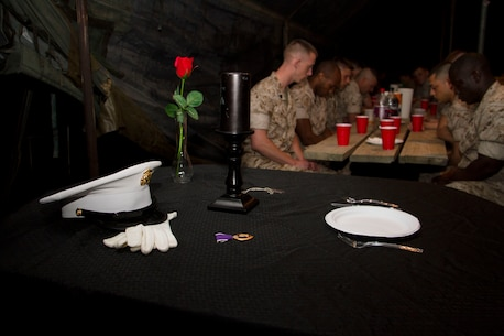 """Marines bow their heads for a moment of silence dedicated to their fallen comrades during Recruiting Station Milwaukee's mess night, June 11, 2015.  """"The table is draped in black, symbolizing the color of mourning; the ultimate sacrifice, a table set in honor of our fallen comrades."""""""