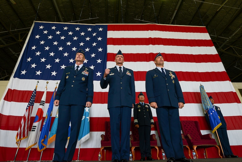 Lt. Gen. Terrence O'Shaughnessy, 7th Air Force commander, Col. Andrew Hansen, incoming 51st Fighter Wing commander, and Col. Brook Leonard, outgoing 51st Fighter Wing commander, sing the Air Force song at the end of the 51st FW change of command ceremony June 16, 2015, at Osan Air Base, Republic of Korea. The ceremony signified the passing of authority in the 51st FW. (U.S. Air Force photo by Staff Sgt. Jake Barreiro/Released)