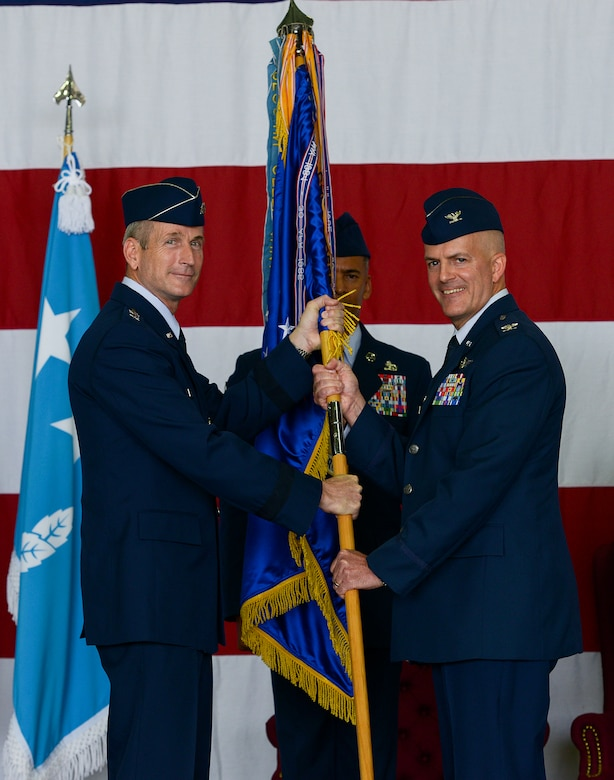 Col. Andrew Hansen, incoming 51st Fighter Wing commander, accepts the guideon and command of the wing from Lt. Gen. Terrence O'Shaughnessy, 7th Air Force commander, during the 51st FW change of command ceremony June 16, 2015, at Osan Air Base, Republic of Korea. Hansen is the 63rd commander in the wing's history. (U.S. Air Force photo by Staff Sgt. Jake Barreiro/Released)