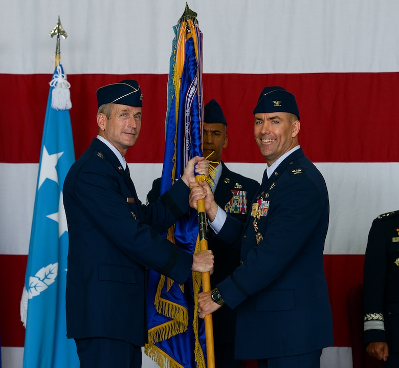 Col. Brook Leonard, outgoing 51st Fighter Wing commander, hands off the guideon to Lt. Gen. Terrence O'Shaughnessy, 7th Air Force commander, during the 51 FW change of command ceremony June 16, 2015, at Osan Air Base, Republic of Korea. Leonard began his command tour in July of 2013. (U.S. Air Force photo by Staff Sgt. Jake Barreiro/Released)