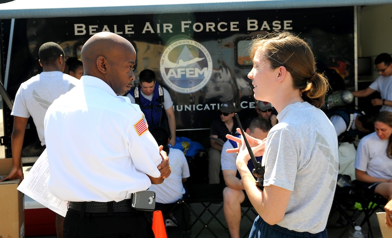 SSgt Michaela Spiegle (right), 9th Aerospace Medicine Squadron bioenvironmental engineering technician, briefs Carey Waddell, 9th Civil Engineer Squadron exercise incident commander, as part of an exercise on June 11, 2015 at Beale Air Force Base, California. The exercise was part of the Integrated Base Emergency Response Capabilities Training designed to strengthen Airmen's emergency response skills. (U.S. Air Force photo by Airman Preston L. Cherry/Released)