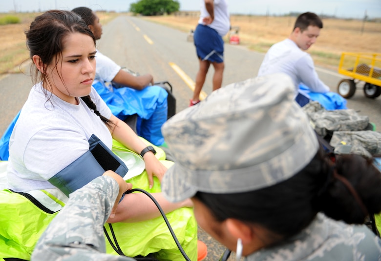 A Beale Airman receives a medical examination during a simulated hazardous scene as part of an exercise on June 10, 2015 at Beale Air Force Base, California. The exercise was part of the Integrated Base Emergency Response Capabilities Training designed to strengthen Airmen's emergency response skills. (U.S. Air Force photo by Airman Preston L. Cherry/Released)