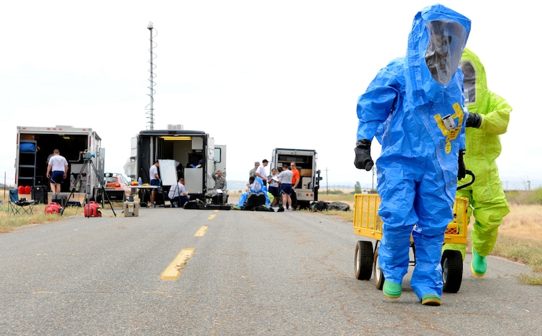 Airman 1st Class Robert Rybicky (left), 9th Aerospace Medicine Squadron bioenvironmental technician, and Senior Airman Kent Hunter, 9th Civil Engineer Squadron emergency management technician, walk to a simulated hazardous scene for an exercise on June 10, 2015 at Beale Air Force Base, California. The exercise was part of the Integrated Base Emergency Response Capabilities Training designed to strengthen Airmen's emergency response skills. (U.S. Air Force photo by Airman Preston L. Cherry/Released)
