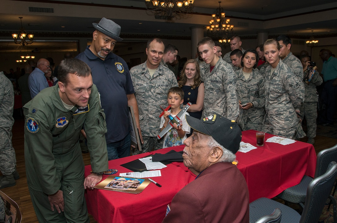 Members of the JBSA-Randolph community listen to Mr. Thomas M. Ellis, documented original Tuskegee Airmen, speak about his time serving with the Tuskegee Airmen during the Tuskegee Airmen Tribute, June 12, 2015, at Joint Base San Antonio-Randolph's Parr Club.  Members of the JBSA-Randolph community celebrated the legacy of the first all-black unit by paying tribute to seven of the documented original Tuskegee Airmen members.  The Tuskegee Airmen distinguished themselves during World War II with more than 15,500 sorties and 1,500 missions in Europe and North Africa and earned numerous combat awards.  The event featured musical entertainment, comments by 12th Flying Training Wing leaders, an introduction of four Tuskegee Airmen present and a presentation of gifts to them. Members of the audience had an opportunity to mingle with the Tuskegee Airmen and listen to their stories. (U.S. Air Force photo by Johnny Saldivar/released)