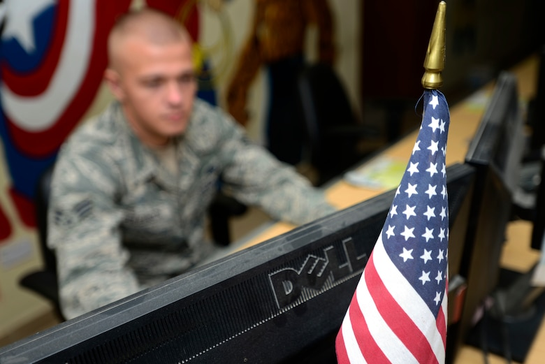 U.S. Air Force Senior Airman Vadim Poleanschi, a 386th Expeditionary Logistic Readiness Squadron logistic specialist, displays an American flag behind his computer monitor at an undisclosed location in Southwest Asia on June 3, 2015. Poleanschi applied to become a United States citizen in late 2013, after joining the AF. (U.S. Air Force photo by Senior Airman Racheal E. Watson/Released)