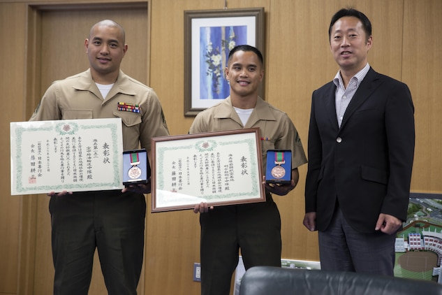 Sgt. Carlos Notarianni, left, the representative for VMGR-152, Lance Cpl. Adam Gordy, middle, the representative for H&HS, and Yoshihiko Fukuda, right, mayor of Iwakuni City, pose for a picture after their meeting at city hall June 3, 2015. The representatives went to city hall to report to the mayor after receiving awards from the Japan Good Deeds Association during their 65th Spring Commendation Ceremony in May. H&HS and VMGR-152 received the awards for assisting the local community whose homes were affected by a mudslide in August 2014.