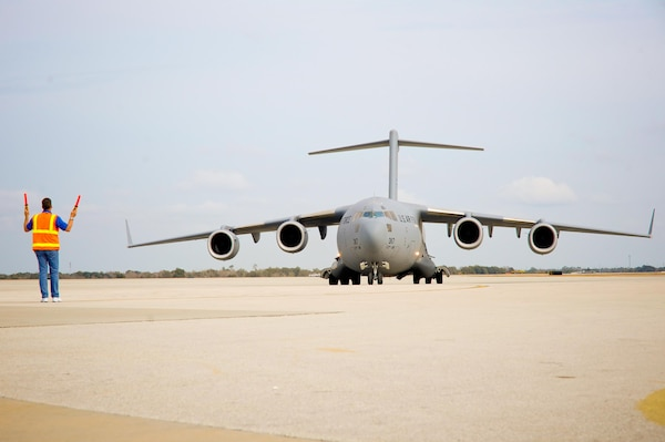 A C-17 Globemaster III from the Mississippi Air National Guard is being directed to park at Orlando Sanford International Airport, Jan. 21, 2010. The C-17 was carrying over 50 evacuees from Haiti.