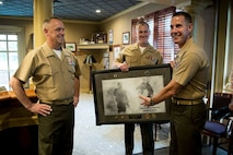 Brigadier General Kevin Killea (left), the Futures Directorate Director and Commanding General of the Warfighting Laboratory is presented with a parting gift from the Futures Directorate by Deputy Director Colonel Jeff Holt (right) and Captain Jerald Feehery (center).  An early summer Hail and Farewell was hosted at the Clubs at Quantico Friday June 12 to formally welcome a few new members of the team and to say farewell and thank you to those moving on to the next phase of their lives and military careers.