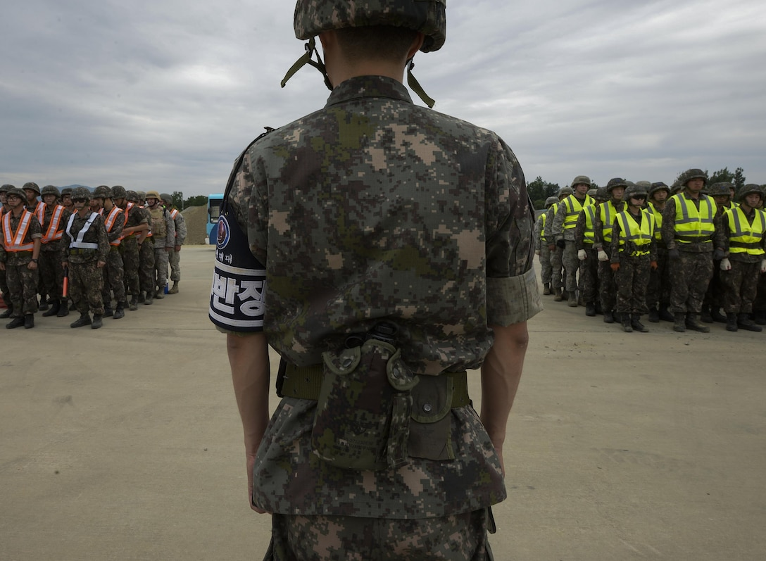 Civil engineer service members from the U.S. and South Korea assemble in formation before being dispatched to repair a runway for exercise Pacific Unity, June 11, 2015, at Jungwon Air Base, South Korea. The goal of Pacific Unity was to develop U.S. Air Force and South Korea engineer interoperability for rapid responses to contingency and disaster response events. (U.S. Air Force photo/Staff Sgt. Jake Barreiro)