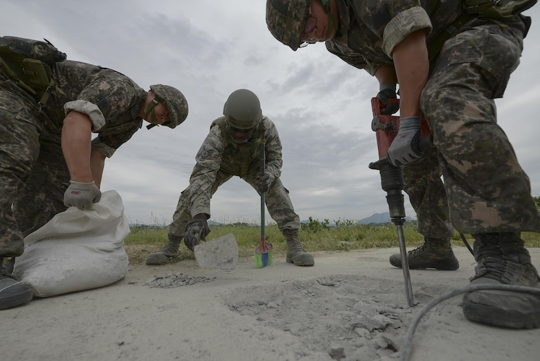 Airmen from the U.S. and South Korea work together to repair a damaged runway during exercise Pacific Unity, June 11, 2015, at Jungwon Air Base, South Korea. The exercise was designed to give U.S. and South Korean airmen the chance to further develop their international relationship by networking and exchanging information, while working together in a simulated contingency. (U.S. Air Force photo/Staff Sgt. Jake Barreiro)
