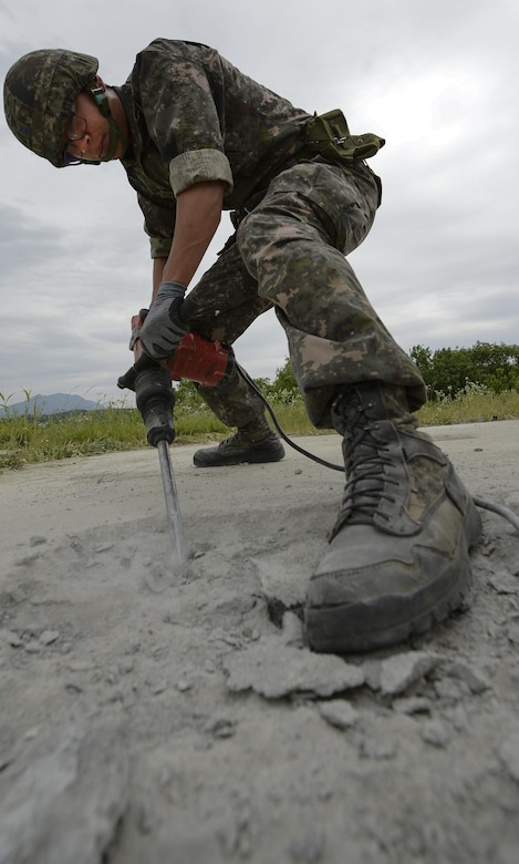 A South Korea air force civil engineer drills concrete during an airway damage repair scenario for Pacific Unity, June 11, 2015, at Jungwon Air Base, South Korea. The scenario simulated an attack that disabled a functioning airfield, with U.S. and South Korea Airmen having to work together to repair the airway to functionality. (U.S. Air Force photo/Staff Sgt. Jake Barreiro)