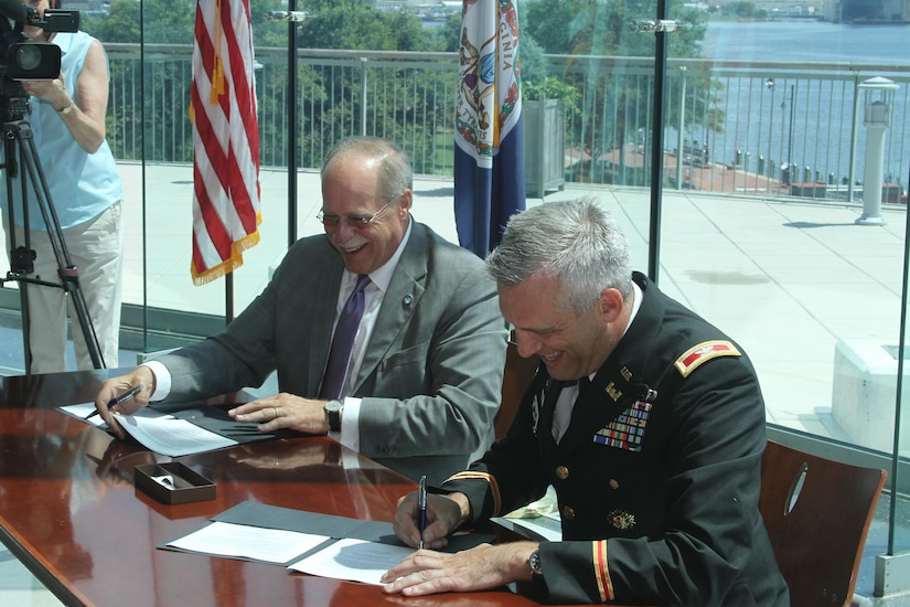John Reinhart, CEO and executive director of the Virginia Port Authority and Colonel Paul Olsen, Norfolk District, U.S. Army Corps of Engineer's former commander, sign the feasibility cost-share agreement, which commits each side to sharing the cost of evaluating the benefits of two dredging projects critical to the future of Norfolk Harbor.