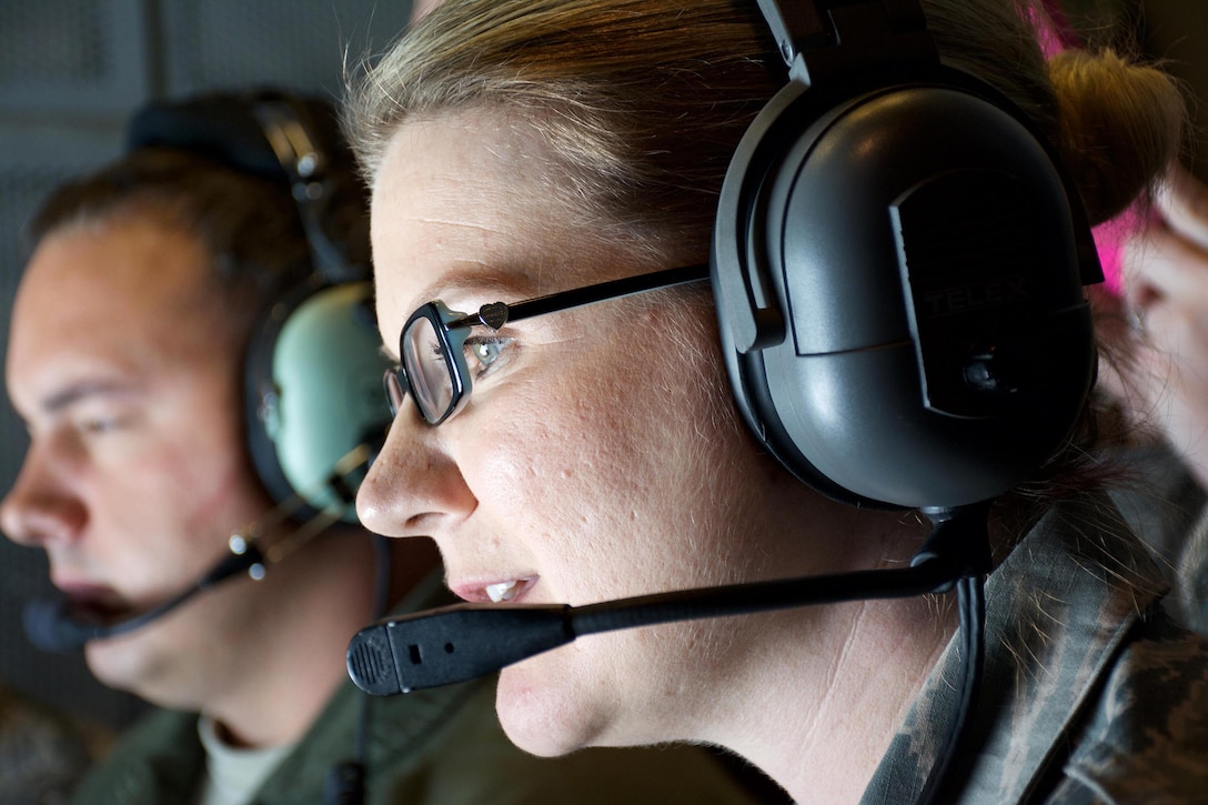 Master Sgt. Leanna Jack looks on as a C-5M Super Galaxy connects with a KC-10 Extender June 6, 2015 over San Francisco. Jack was one of more than 15 Air Force Reservists, assigned to the 349th Air Mobility Wing at Travis Air Force Base, California, who took part in an orientation flight. The flight allowed wing top performers to experience the wing's aerial refueling mission. During the weekend, the 349th AMW hosted an Air Force Speciality Code Training Weekend, providing reservists with hands-on, realistic training that helps members hone their skills. The AFSC Training Weekend centered around the wing's ability to respond to a major earthquake in northern California, while working in concert with other military, federal and state agencies to provide relief and support where needed. (U.S. Air Force photo by 2nd Lt. Stephen J. Collier/Released)