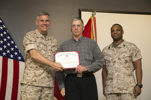 United States Marine Corps Forces Special Operations Command Commander Maj. Gen. Joseph L. Osterman and Sgt. Maj. John W. Scott, the MARSOC sergeant major, present Glenn C. Wright, Jr., a Certificate of Commendation during the MARSOC annual awards ceremony at Stone Bay, aboard Marine Corps Base Camp Lejeune, N.C., June 3, 2015. Wright was selected as the 2014 MARSOC Civilian of the Year. (U.S. Marine Corps photo by Sgt. Scott A. Achtemeier/Released)