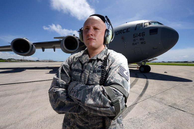 U.S. Air Force Tech. Sgt. David Williamson, 733rd Air Mobility Squadon, stands next to a 36th Airlift Squadron C-17 Globemaster III cargo aircraft on the Kadena Air Base, Japan, flightline June 9, 2015. In addition to the hard work he puts into his Air Force career, Williamson also strives to improve his rap career outside the uniform. (U.S. Air Force photo by Staff Sgt. Maeson L. Elleman)
