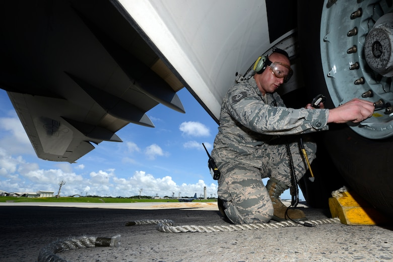 U.S. Air Force Tech. Sgt. David Williamson, 733rd Air Mobility Squadon, checks the air pressure in the tire of a 36th Airlift Squadron C-17 Globemaster III cargo aircraft on the Kadena Air Base, Japan, flightline June 9, 2015. In addition to the hard work he puts into his Air Force career, Williamson also strives to improve his rap career outside the uniform. (U.S. Air Force photo by Staff Sgt. Maeson L. Elleman)
