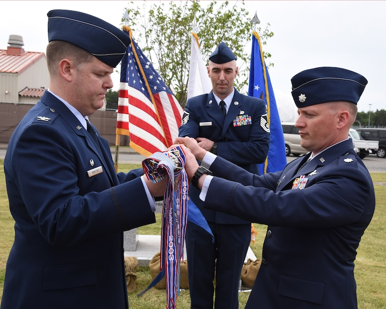 Col. Michael Winters, 373d ISR Group commander, and Lt. Col. Jonathan Boling, 373 Support Squadron commander, furl the 373d Support Squadron guidon during the unit's inactivation ceremony June 2, 2015, atop Security Hill at Misawa Air Base, Japan. (Courtesy photo)