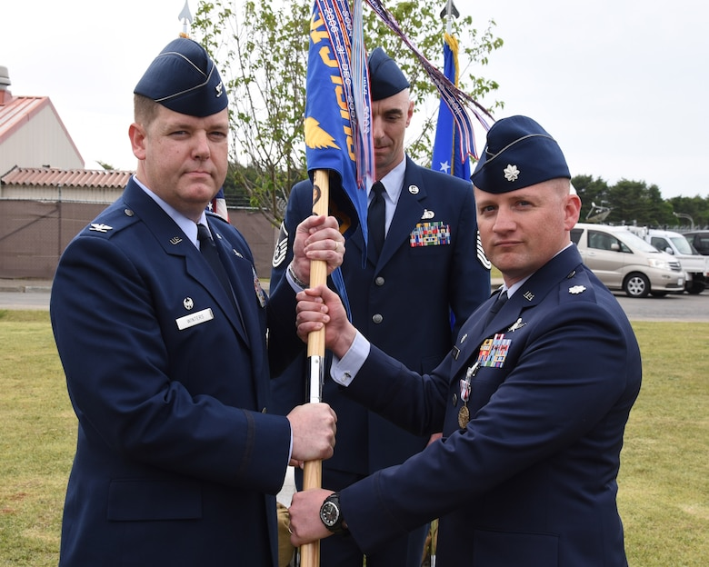 Col. Michael Winters, 373d ISR Group commander, and Lt. Col. Jonathan Boling, 373 Support Squadron commander, pause for a photo prior to furling the 373d Support Squadron guidon during the unit's inactivation ceremony June 2, 2015, atop Security Hill at Misawa Air Base, Japan.  (Courtesy photo)