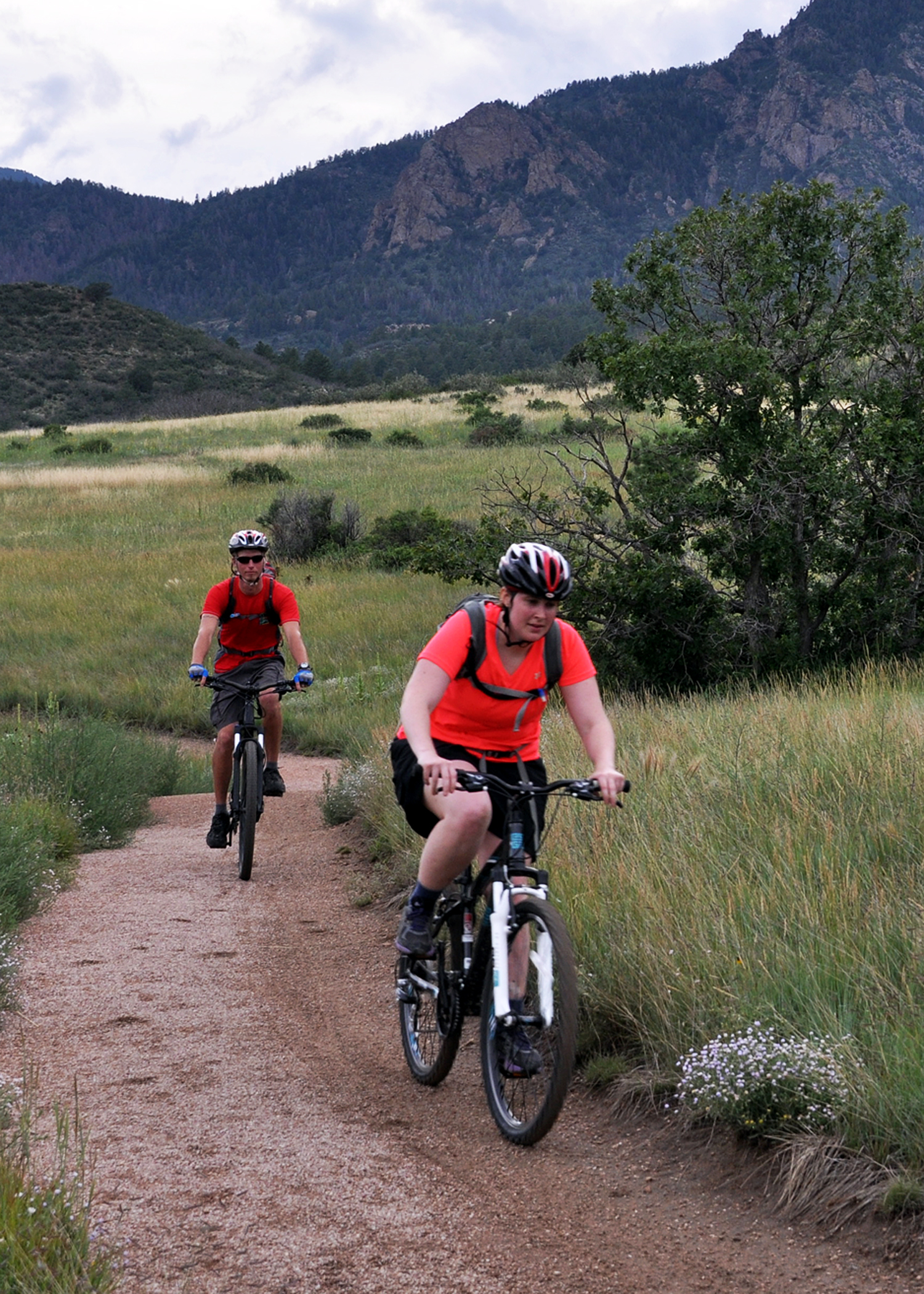 Two people in red shirts on mountain bikes ride on a trail toward the photographer, Rocky Mountains in the background.