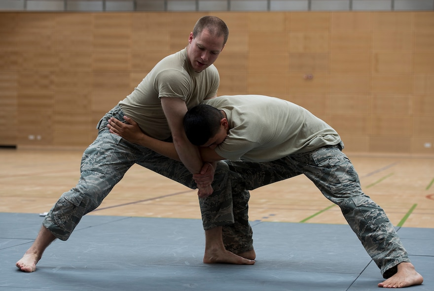 U.S. Air Force Senior Airman Erik Alter, 52nd Security Forces Squadron lead combatives instructor, demonstrates a technique to Airmen from the 52nd SFS during combatives training May 28, 2015 at the fitness center on Spangdahlem Air Base, Germany. Military law enforcement officers conduct regular hand-to-hand combat training to ensure they are prepared for any hostile suspects they might encounter. (U.S. Air Force photo by Staff Sgt. Chad Warren/Released)
