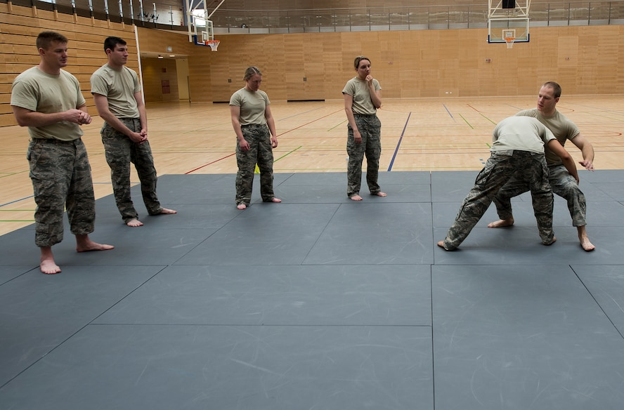 U.S. Air Force Senior Airman Erik Alter, 52nd Security Forces Squadron lead combatives instructor, demonstrates a technique to Airmen from the 52nd SFS during combatives training May 28, 2015 at the fitness center on Spangdahlem Air Base, Germany. All law enforcement officers assigned to the 52nd SFS are required to complete basic hand-to-hand combat training, meant to prepare them for any unexpected encounters on the job. (U.S. Air Force photo by Staff Sgt. Chad Warren/Released)