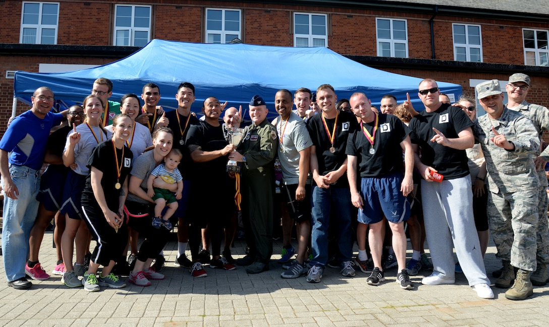 U.S. Air Force Airmen from the 100th Air Refueling Wing staff agencies pose for a photo after winning the Marauder Melee sports competition June 11, 2015, on RAF Mildenhall, England. After a 5k run, the event  consisted of  several fitness challenges including volleyball, soccer and rock climbing, of which Wing Staff Agency teams either won first or second place earning them the most overall points amongst several groups and squadrons. (U.S. Air Force photo by Senior Airman Kate Thornton/Released)