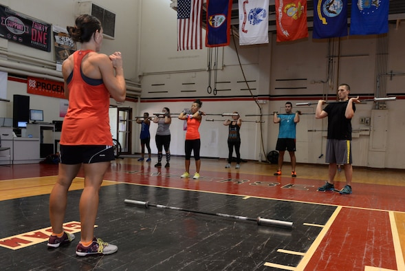Team Andersen members learn how to execute a clean using proper form June 15, 2015, at the functional fitness gym on Andersen Air Force Base, Guam. CrossFit-certified trainers continue to keep an eye on gym members to track progress, make sure they're doing the movements correctly and make sure they are comfortable performing the exercises. (U.S. Air Force photo by Airman 1st Class Joshua Smoot/Released)