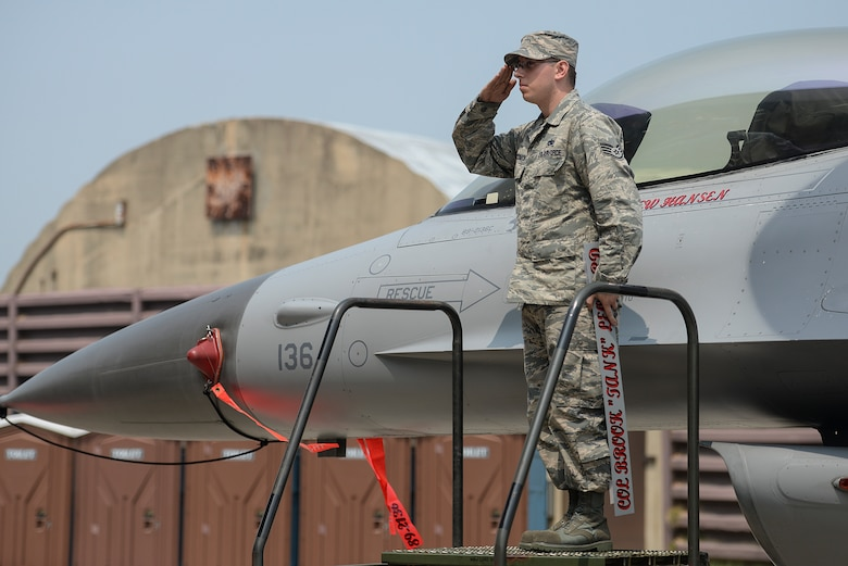 Staff Sgt. Patrick McCormick, 51st Aircraft Maintenance Squadron dedicated crew chief, salutes the new 51st Fighter Wing commander during the 51st FW Change of Command ceremony, June 16, 2015, at Osan Air Base, Republic of Korea. The Change of Command ceremony is a military tradition that represents a formal transfer of authority and responsibility for a unit from one commanding officer to another. (U.S. Air Force photo by Senior Airman Matthew Lancaster)