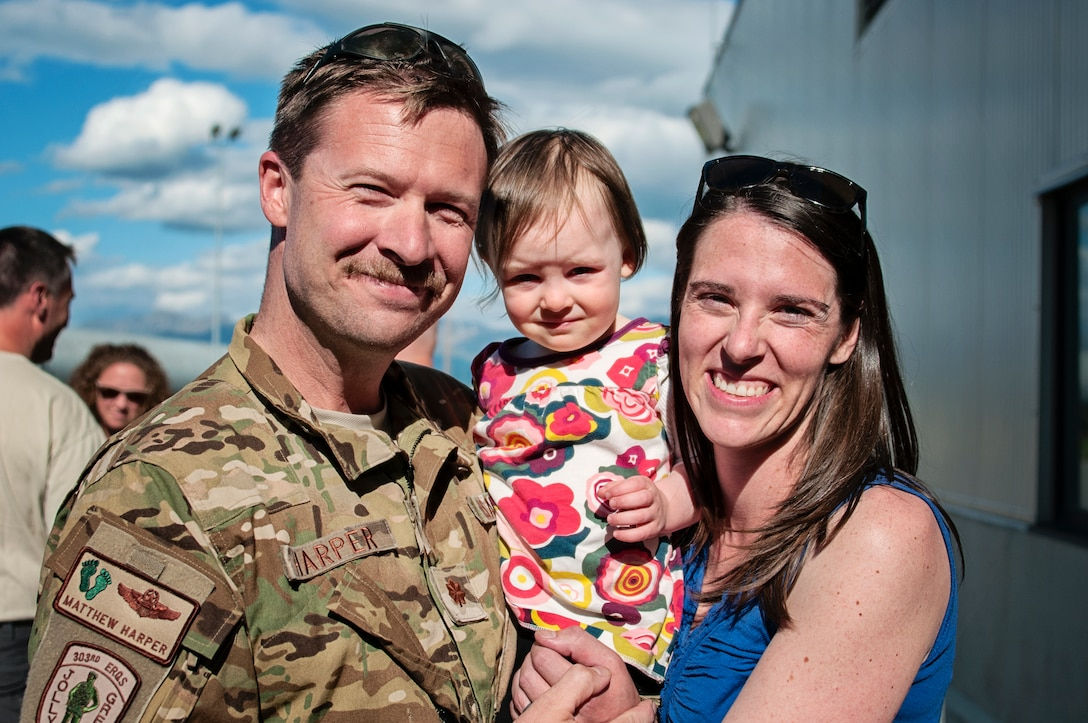 Alaska Air National Guardsman Maj. Matthew Harper, with the 210th Rescue Squadron, poses for a photo with his family at Joint Base Elmendorf-Richardson, June 12. Harper, along with 15 additional Guardsmen from the 176th Operations Group, the 210th Rescue Squadron, the 211th Rescue Squadron and the 176th Logistics Readiness Squadron, returned from a four month deployment to Djibouti in support of Operation Enduring Freedom. (Air National Guard photo by Staff Sgt. Edward Eagerton/released)