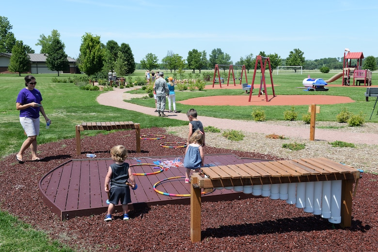 Families explore playground equipment recently installed at Warrior Park after the official ribbon cutting to open the new area June 10. The new additions are geared toward children with disabilities and young children. (U.S. Air Force photo/Senior Airman Joshua Eikren)