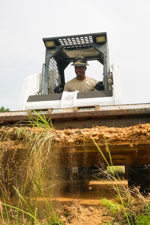 U.S. Air Force Senior Airman Ramirez Edmond, a cable and antenna systems specialist with the 202nd Engineering Installation Squadron (EIS), Georgia Air National Guard, removes dirt from a berm using a Bobcat during a weeklong training exercise at Robins Air Force Base, Ga., June 11, 2015. More than 80 Airmen were certified in career-field tasks crucial to the unit's deployed and homeland missions. The 202nd EIS supports the 116th Air Control Wing and is responsible for the fixed-communications infrastructures for 27 other locations, including the 165th Airlift Wing in Savannah, Georgia, and Air National Guard units in Puerto Rico and the U.S. Virgin Islands. (U.S. Air National Guard photo by Senior Master Sgt. Roger Parsons/Released)
