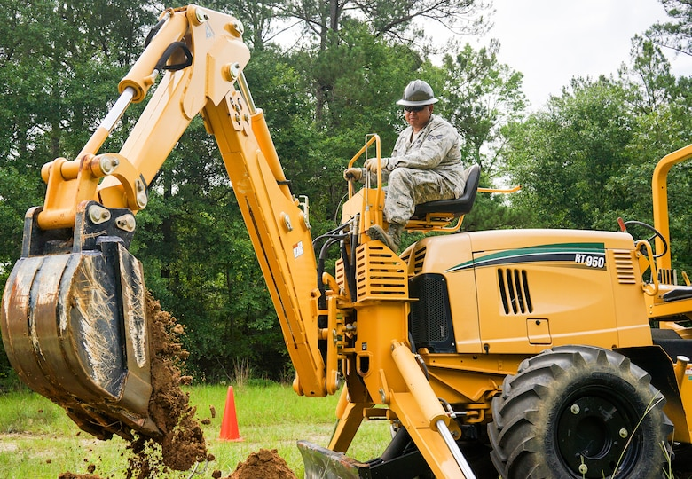 U.S. Air Force Staff Sgt. Chymann Lao, a cable and antenna systems specialist with the 202nd Engineering Installation Squadron (EIS), Georgia Air National Guard, digs a trench using a trencher with a backhoe attachment during a weeklong training exercise at Robins Air Force Base, Ga., June 11, 2015. More than 80 Airmen were certified in career-field tasks crucial to the unit's deployed and homeland missions. The 202nd EIS supports the 116th Air Control Wing and is responsible for the fixed-communications infrastructures for 27 other locations, including the 165th Airlift Wing in Savannah, Georgia, and Air National Guard units in Puerto Rico and the U.S. Virgin Islands. (U.S. Air National Guard photo by Senior Master Sgt. Roger Parsons/Released)