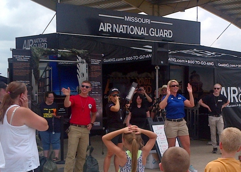 Airman 1st Class Albert Fleer (red shirt), aerospace ground equipment technician from the 131st Maintenance Squadron, and Master Sgt. Melissa Lakin, 131st Bomb Wing recruiting supervisor, get a large crowd pumped up at the Missouri Air National Guard recruiting trailer at the Wings Over Whiteman air show here June 13, 2015.  A number of Citizen-Airmen from the wing were on hand to support the two-day air show event.  (U.S. Air National Guard photo by Capt. Jeffrey Bishop)