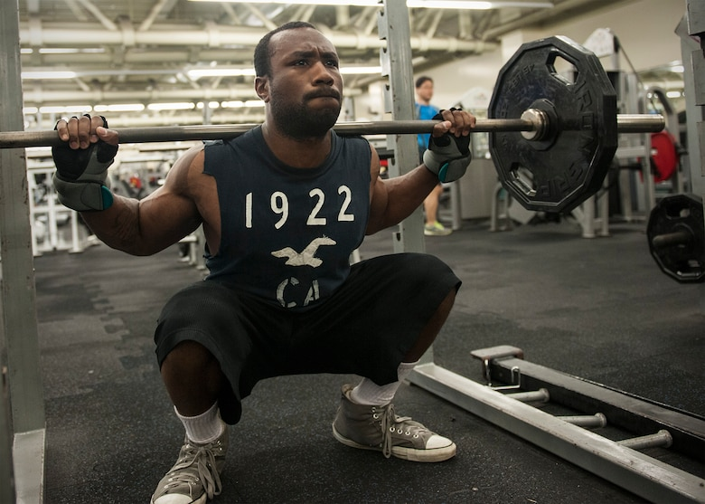 Senior Airman Stephen Caseman, 8th Maintenance Group weapons standardization technician, demonstrates a barbell squat at the Kunsan Fitness Center, Kunsan Air Base, Republic of Korea, June 12, 2015. According to Bill Goins, 8th Medical Operations Squadron health promotions coordinator, Airmen should strength train two to three days a week per muscle group; with two to three sets of eight to 12 repetitions [regardless of gender or fitness level], starting with the largest muscles first. (U.S. Air Force photo by Senior Airman Katrina Heikkinen/Released)