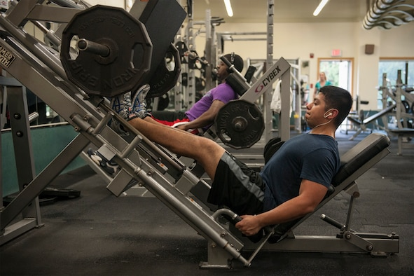 Senior Airman George Gonzales, 8th Maintenance Squadron electronics warfare technician, leg presses 200 pounds at the Kunsan Fitness Center, Republic of Korea, June 12, 2015. The 8th Medical Operations Squadron health promotions office offers strength training 101, a class that teaches Airmen the basics of incorporating effective strength training exercises in their personal fitness program. (U.S. Air Force photo by Senior Airman Katrina Heikkinen/Released)