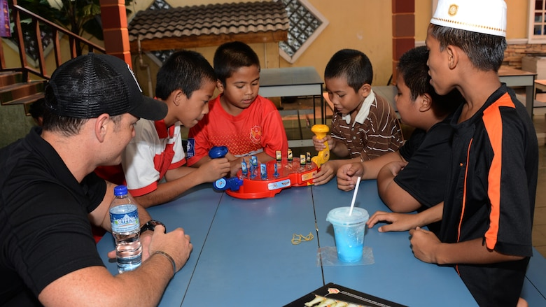 U.S. Air Force Capt. Forrest Underwood, a pilot from the 17th Special Operations Squadron, plays games with boys from the Rumah Kasih Hormoni Orphanage near Kuala Lumpur, Malaysia, June 6, 2015.  As part of Exercise Teak Mint, members from the RMAF, U.S. Air Force came together to help with repairs around the orphanage and donated more than  $1,000 in clothes, games and sports equipment.  (U.S. Air Force photo by Tech. Sgt. Kristine Dreyer)