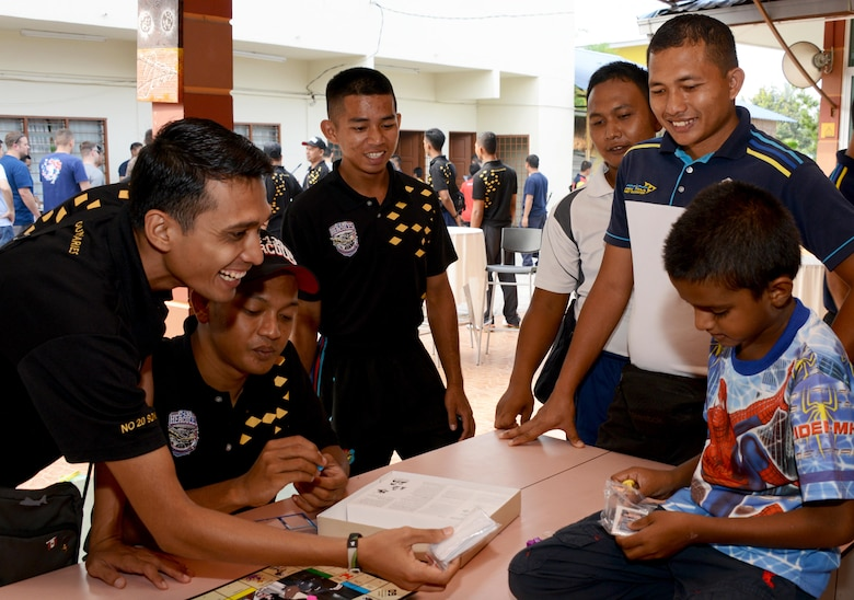 Members from the Royal Malaysian Air Force play a game with a child from the Rumah Kasih Hormoni Orphanage near Kuala Lumpur, Malayasia, June 6, 2015.  As part of Exercise Teak Mint, members from the RMAF, U.S. Air Force came together to help with repairs around the orphanage.  Members from the 353rd Special Operations Group donated more than  $1,000 in clothes, games and sports equipment.   (U.S. Air Force Tech. Sgt. Kristine Dreyer)