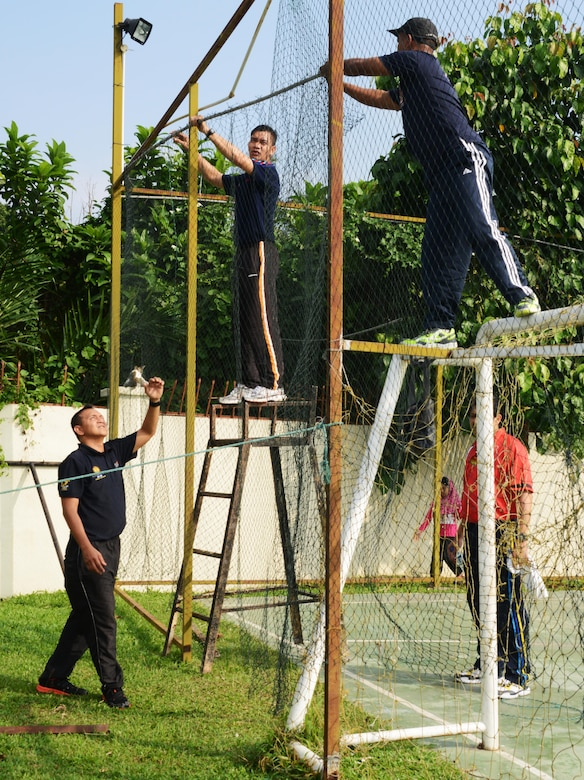 Members from the Royal Malaysian Air Force repair fencing around the soccer pitch at the Rumah Kasih Hormoni Orphanage near Kuala Lumpur, Malayasia, June 6, 2015 As part of Exercise Teak Mint, members from the RMAF, U.S. Air Force came together to help with repairs around the orphanages and  donated more than  $1,000 in clothes, games and sports equipment.  (U.S. Air Force Tech. Sgt. Kristine Dreyer)