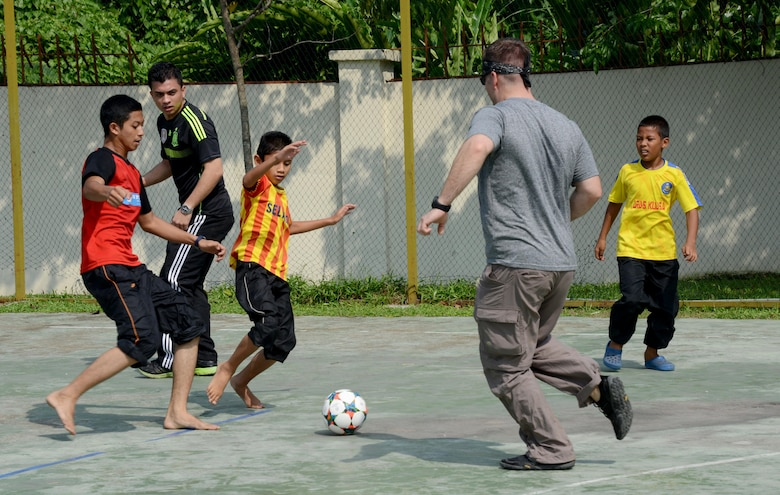 Tech. Sgt. Ryan Moore a loadmaster with the 17th Special Operations Squadron and a member from the Royal Malaysian Air Force play soccer with the children at the Rumah Kasih Hormoni Orphanage near Kuala Lumpur, Malaysia, June 6, 2015.  As part of Exercise Teak Mint, members from the RMAF, U.S. Air Force came together to help with repairs around the orphanage and donated more than $1,000 in clothes, games and sports equipment.  (U.S. Air Force photo by Tech. Sgt. Kristine Dreyer)