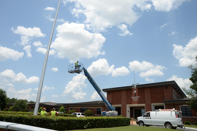 Bubba Hart, technician, Facility Improvement Services, is hoisted approximately 85 feet into the air to investigate a maintenance issue with the flag pole in front of Marine Corps Logistics Base Albany's Coffman Hall, June 17.